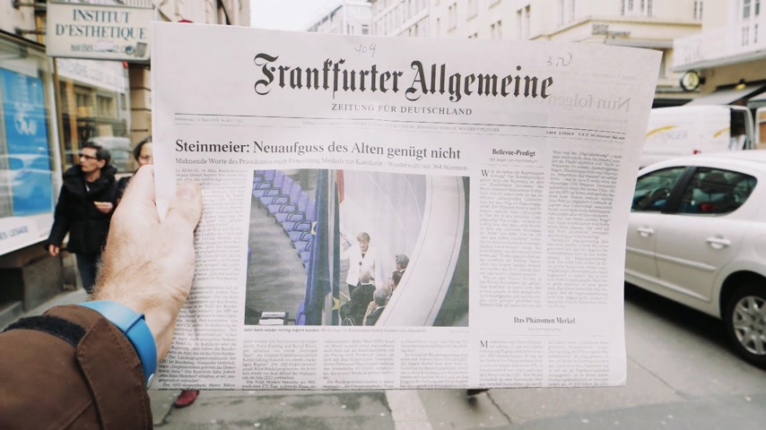 журналистика : PARIS, FRANCE - MAR 15, 2017: Man reading buying German Frankfurter Allgemeine Zeitung newspaper at press kiosk featuring Angela Dorothea Merkel re election as Chancellor of Germany cinematic slow motion pedestrians