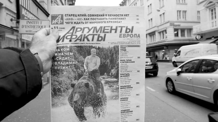 satire : PARIS, FRANCE - MAR 15, 2018: Slow motion Argumenty i Fakty Russian newspaper featuring the photograph of Vladimir Putin on a Siberian grizzly bear before Russian Elections black and white