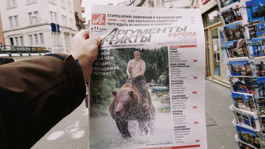 french president : PARIS, FRANCE - MAR 15, 2018: Argumenty i Fakty Russian newspaper featuring the photograph of Vladimir Putin on a Siberian grizzly bear before Russian Elections