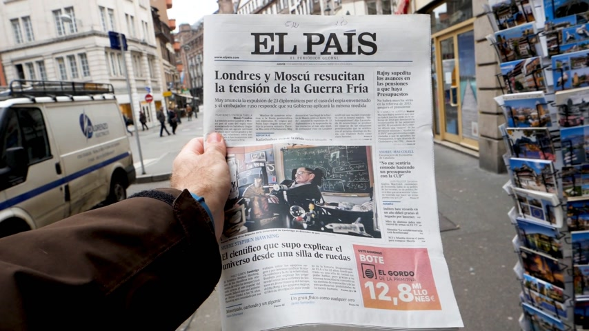 físico : PARIS, FRANCE - MAR 15, 2018: City slow motion with Male hand holding Spanish El Pais newspaper with portrait of Stephen Hawking the English theoretical physicist, cosmologist dead on 14 March 2018 outdoor press kiosk