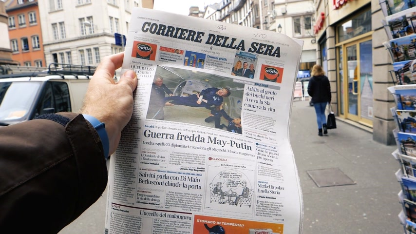 buy newspaper : PARIS, FRANCE - MAR 15, 2018: Italian Corriere della Sera newspaper with portrait of Stephen Hawking the English theoretical physicist, cosmologist dead on 14 March 2018 outdoor press kiosk slow motion Stock Footage