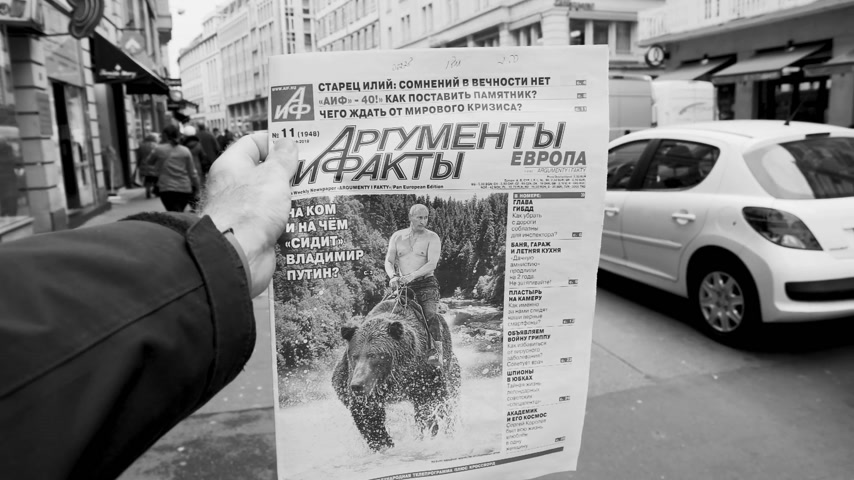 satire : PARIS, FRANCE - MAR 15, 2018: Argumenty i Fakty Russian newspaper featuring the photograph of Vladimir Putin on a Siberian grizzly bear before Russian Elections black and white slow motion Stock Footage