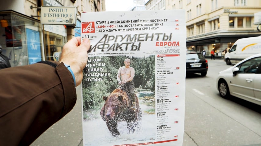 oy : PARIS, FRANCE - MAR 15, 2018: Argumenty i Fakty Russian newspaper featuring the photograph of Vladimir Putin on a Siberian grizzly bear before Russian Elections street slow motion