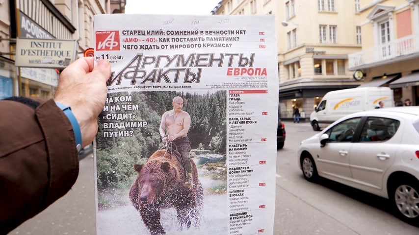 satire : PARIS, FRANCE - MAR 15, 2018: Argumenty i Fakty Russian newspaper featuring the photograph of Vladimir Putin on a Siberian grizzly bear before Russian Elections slow motion