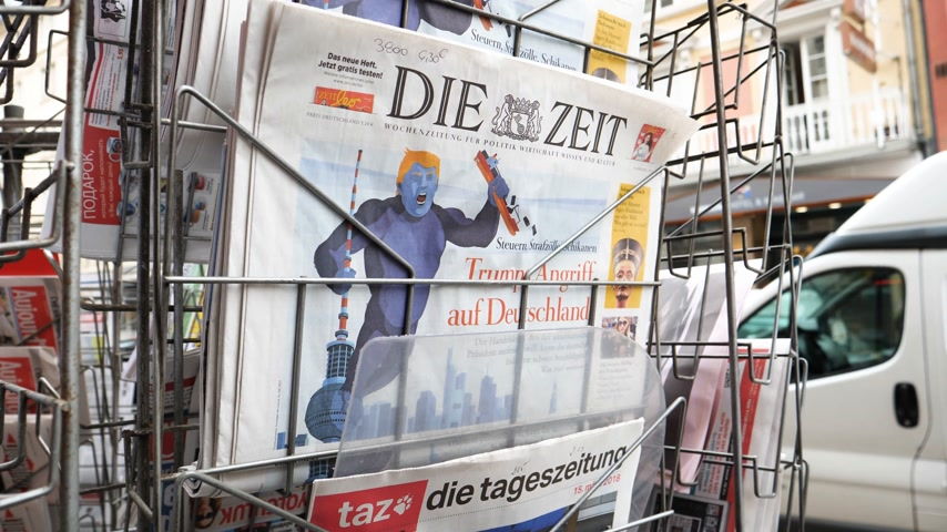 карикатура : PARIS, FRANCE - CIRCA 2018: Press kiosk stand with Die Zeit German newspaper with caricature of Donald Trump and text Trump Attacks Germany
