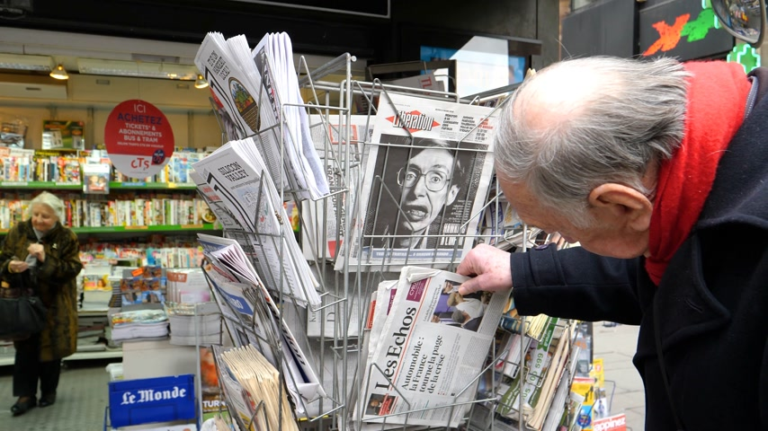 físico : PARIS, FRANCE - MAR 15, 2018: Senior man buying French newspaper Liberation at Parisian press kiosk featuring Stephen Hawking portrait the English theoretical physicist, cosmologist dead on 14 March 2018 outdoor press kiosk Vídeos
