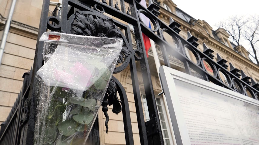 flag half mast : STRASBOURG, FRANCE - MAR 28, 2018: Tilt-down to flowers, toys at entrance of Russian Consulate Embassy mourning of victims of fire at Zimnyaya Vishnya Winter Cherry shopping centre Kemerovo