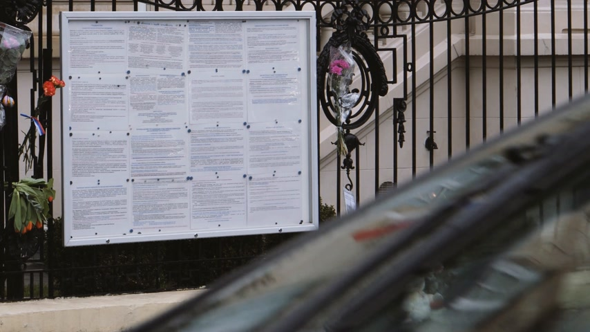 flag half mast : STRASBOURG, FRANCE - MAR 28, 2018: Cars in front of flowers, toys at entrance of Russian Consulate Embassy mourning of victims of fire at Zimnyaya Vishnya Winter Cherry shopping centre Kemerovo