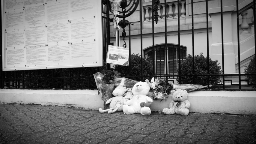 flag half mast : STRASBOURG, FRANCE - MAR 28, 2018: Pedestrian walking near toys and flowers near Russian Consulate Embassy mourning victims fire Zimnyaya Vishnya shopping centre Kemerovo slow motion black and white Stock Footage