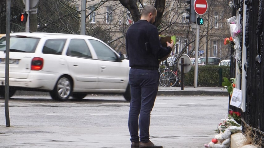 symbol of respect : STRASBOURG, FRANCE - MAR 28, 2018: Man posing flower next toys at Russian Consulate Embassy - mourning of victims fire at Zimnyaya Vishnya Winter Cherry shopping centre Kemerovo Russia - rainy day