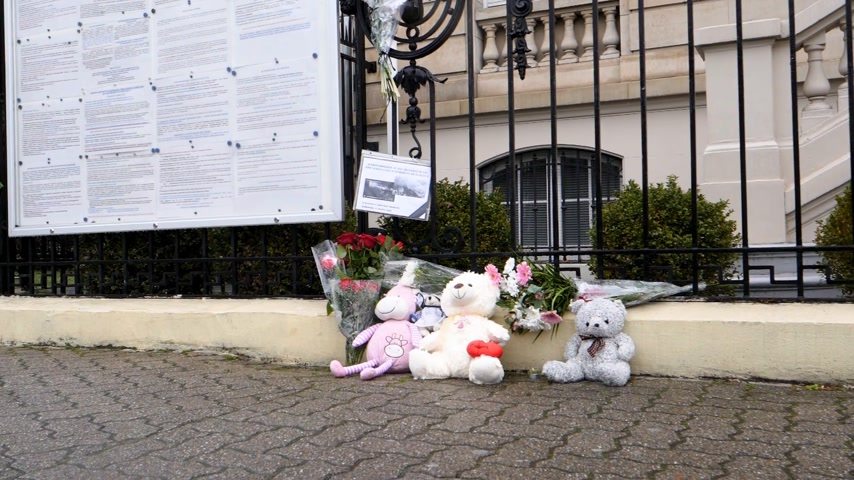 flag half mast : STRASBOURG, FRANCE - MAR 28, 2018: Pedestrian walking near toys and flowers near Russian Consulate Embassy mourning victims fire at Zimnyaya Vishnya Winter Cherry shopping centre Kemerovo slow motion