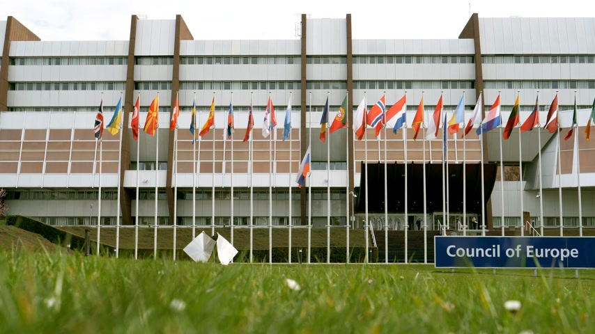 coe : View from below through green grass of Council of Europe building with Flag of Russia flying half-mast as tribute and mourning of victims of fire at Zimnyaya Vishnya shopping centre Kemerovo