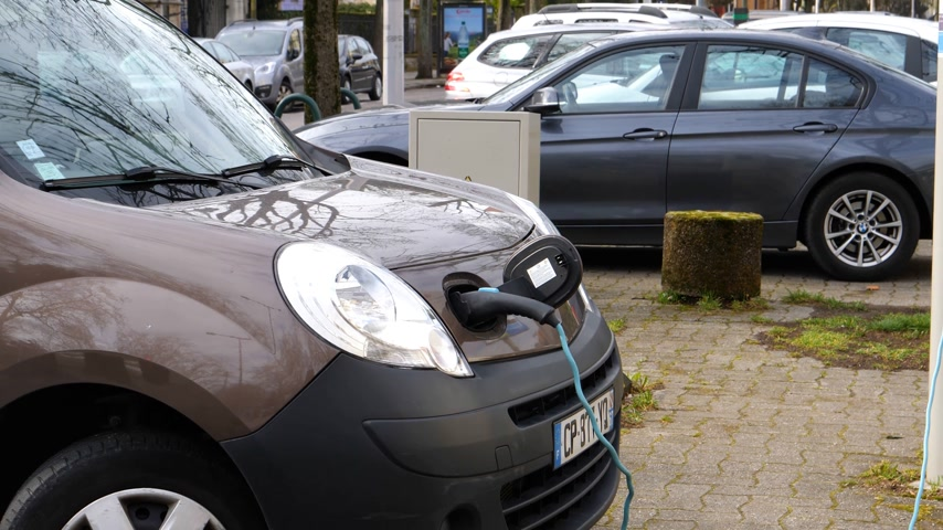 recharging : STRASBOURG, FRANCE - CIRCA 2018: Plugged in Renault mini-van electric car on the street electric car charging station recharging slowly on the street in France