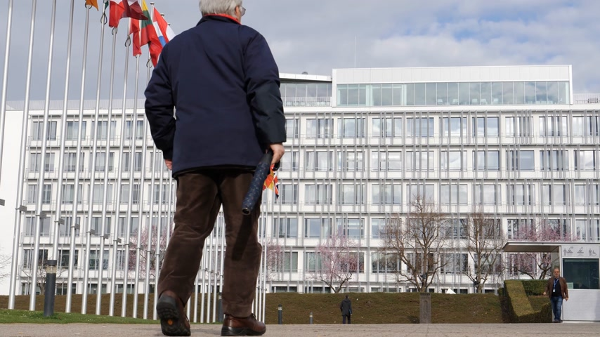national day of mourning : STRASBOURG, FRANCE - MAR 29, 2018: Senior man going to work at Council of Europe with Flag of Russia flying half-mast as tribute and mourning of victims of fire at shopping centre Kemerovo