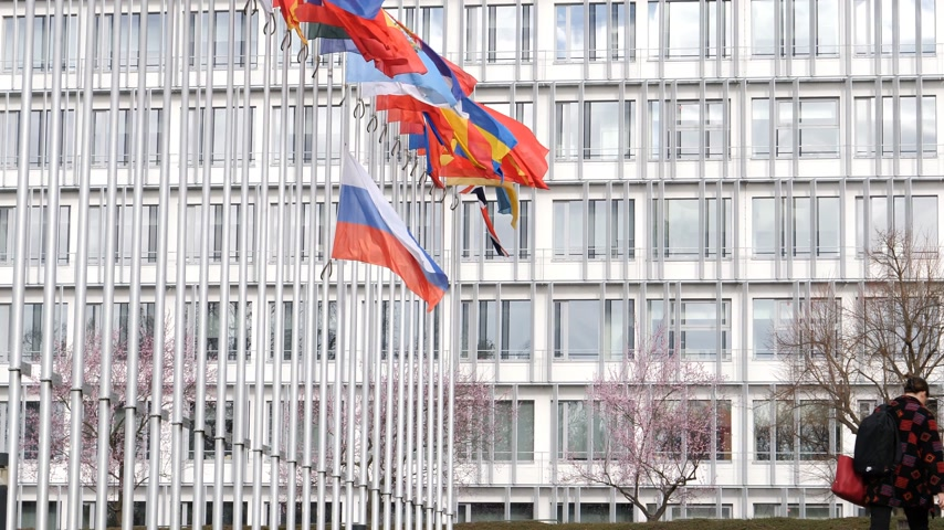 national day of mourning : STRASBOURG, FRANCE - MAR 29, 2018: Woman going to work at Council of Europe with Flag of Russia flying half-mast as tribute and mourning of victims of fire at shopping centre Kemerovo