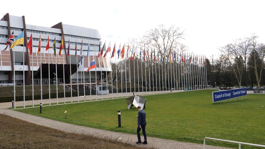 flag half mast : STRASBOURG, FRANCE - MAR 29, 2018: Business man with phone near Council of Europe building with Flag of Russia flying half-mast as tribute and mourning of victims of fire at Zimnyaya Vishnya shopping centre Kemerovo