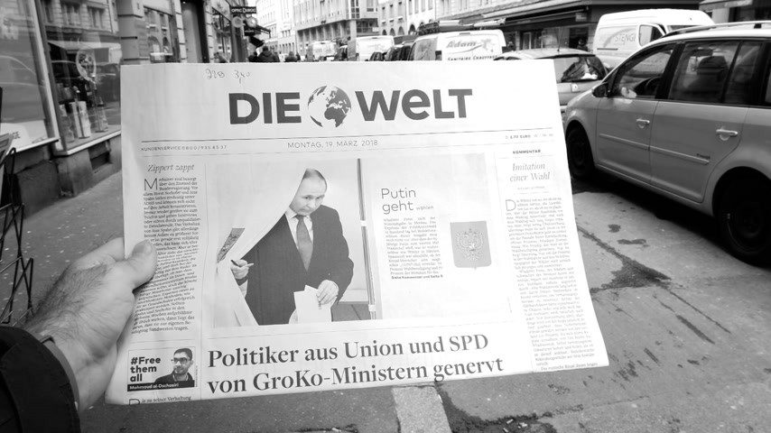 authoritarian state : PARIS, FRANCE - MAR 19, 2017: Man reading buying German Die Welt newspaper at press kiosk featuring Russian presidential election from 2018 with the winner Vladimir Putin city background black and white