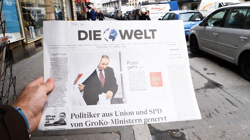 authoritarian state : PARIS, FRANCE - MAR 19, 2017: Man reading buying German Die Welt newspaper at press kiosk featuring Russian presidential election from 2018 with the winner Vladimir Putin city background  - Putin voting