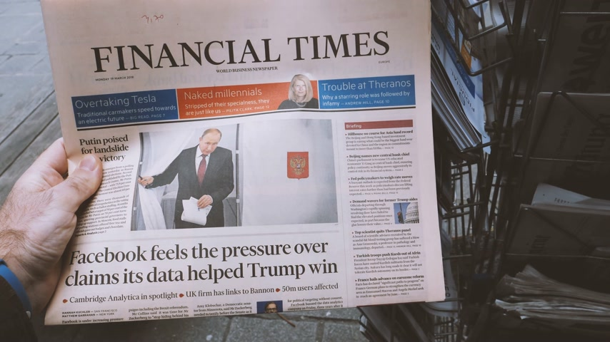authoritarian state : PARIS, FRANCE - MAR 19, 2017:  British Financial Times newspaper at press kiosk featuring Russian presidential election from 2018 with the winner Vladimir Putin - man reading