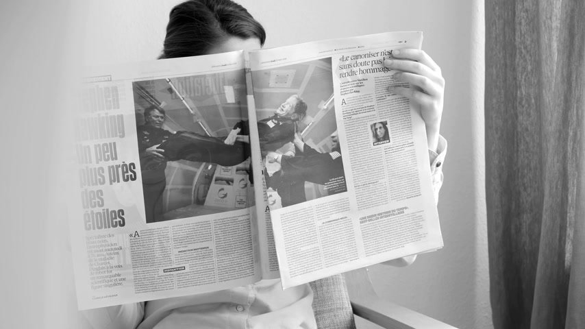 físico : PARIS, FRANCE - MAR 15, 2018: Elegant young woman reading The Times newspaper with portrait of Stephen Hawking English theoretical physicist, cosmologist dead 14 March 2018 black and white