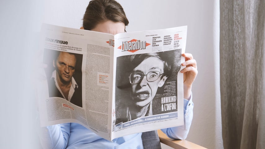 físico : PARIS, FRANCE - MAR 15, 2018: Elegant young woman reading Liberation newspaper with portrait of Stephen Hawking English theoretical physicist, cosmologist dead 14 March 2018