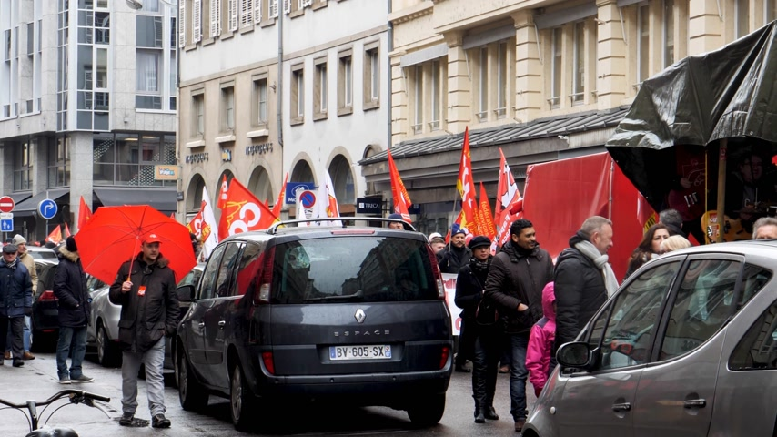 anti macron : STRASBOURG, FRANCE - MAR 22, 2018: Slow walking at general nationwide protest of workers at demonstration protest against Macron French government string of reforms