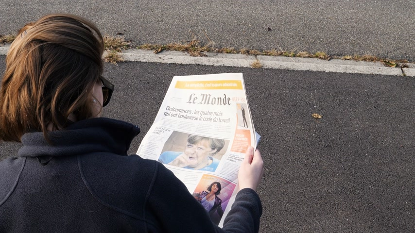 democrats : PARIS, FRANCE - SEP 24, 2017: View from above woman reading latest newspaper Le Monde with portrait of Angela Merkel before the election in Germany for the Chancellor of Germany