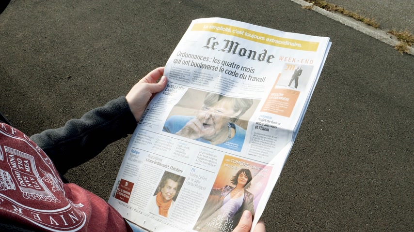 democrats : PARIS, FRANCE - SEP 24, 2017: View from above of woman reading latest newspaper Le Monde with portrait of Angela Merkel before the election in Germany for the Chancellor of Germany, the head of the federal government