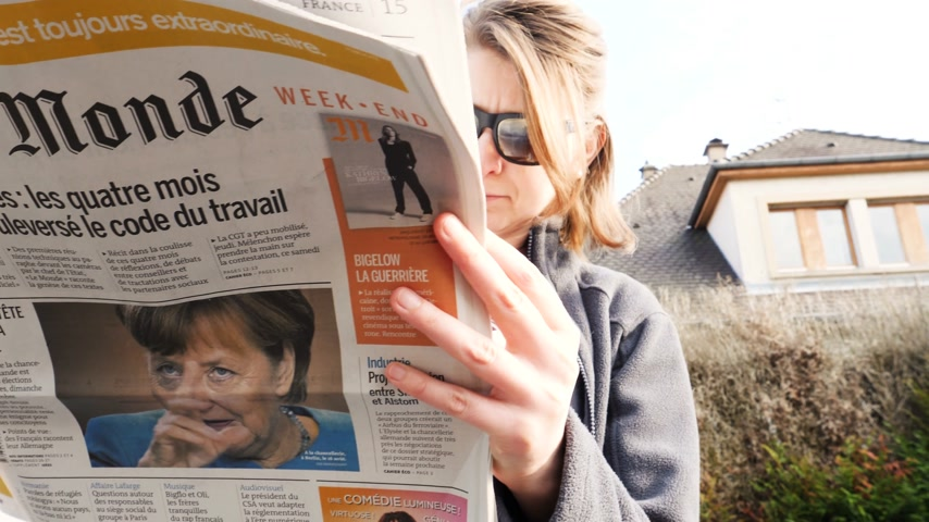 chancellery : PARIS, FRANCE - SEP 24, 2017: Woman reading latest newspaper Le Monde with portrait of Angela Merkel before the election in Germany for the Chancellor of Germany, the head of the federal government Stock Footage