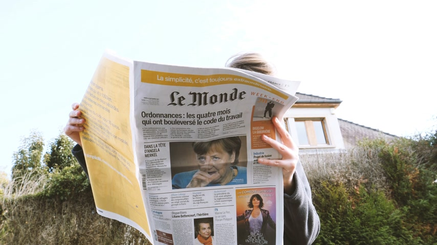 democrats : PARIS, FRANCE - SEP 24, 2017: View from below of woman reading latest newspaper Le Monde with portrait of Angela Merkel before the election in Germany for the Chancellor of Germany, the head of the federal government