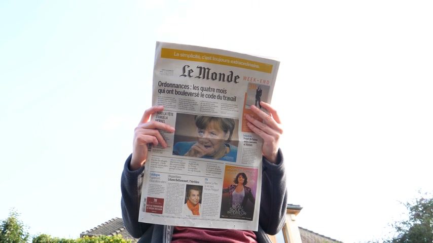 chancellery : PARIS, FRANCE - SEP 24, 2017: View from below of woman reading latest newspaper Le Monde with portrait of Angela Merkel before the election in Germany for the Chancellor of Germany, the head of the federal government