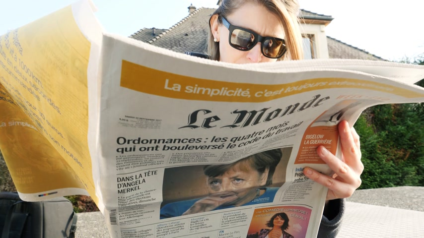 democrats : PARIS, FRANCE - SEP 24, 2017: View from below of curious woman reading latest newspaper Le Monde with portrait of Angela Merkel before the election in Germany for the Chancellor of Germany Stock Footage