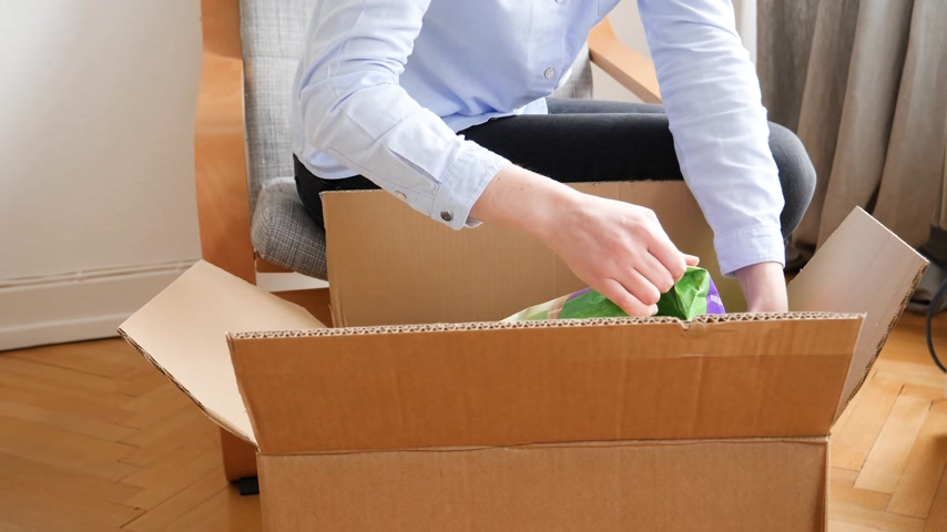 curioso : PARIS, FRANCE - CIRCA 2018: Woman unboxing a freshly large received cardboard box containing cat pet food Royal Canin, toys, litter material - fast motion time lapse
