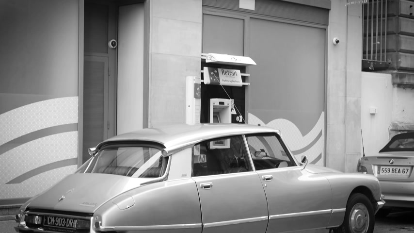 citroen : STRASBOURG, FRANCE - CIRCA 2018: Tilt down to BNP Paribas bank branch and Vintage Citroen DS 23 front-wheel-drive luxury executive car parked in front  ATM bank teller machine - black and white Stock Footage
