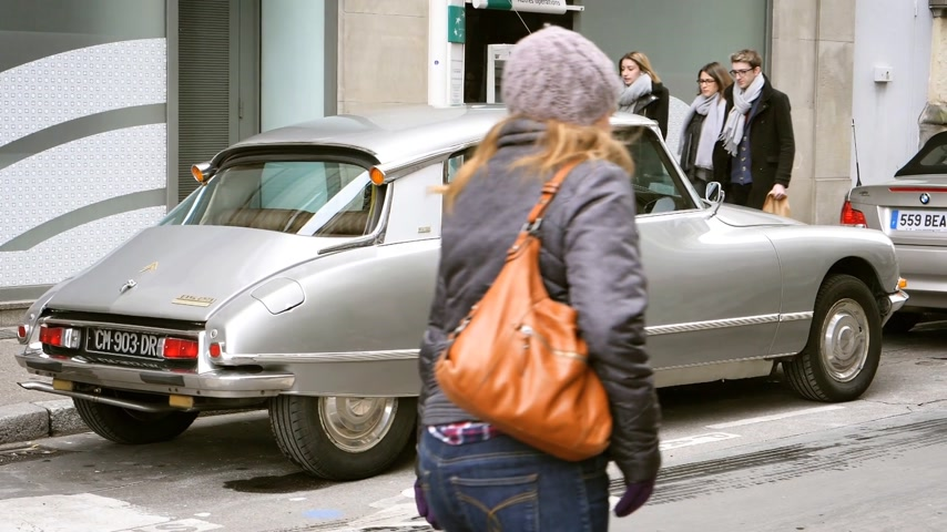 citroen : STRASBOURG, FRANCE - CIRCA 2018: Vintage Citroen DS 23 front-wheel-drive luxury executive car parked in front of a BNP Paribas ATM bank branch with young pedestrians walking in slow motion