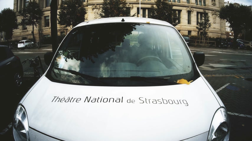 auto parking : STRASBOURG, FRANCE - CIRCA 2018: Cinematic footage Theatre National de Strasbourg signage on the front part of a mini van parked in front of the Theater building