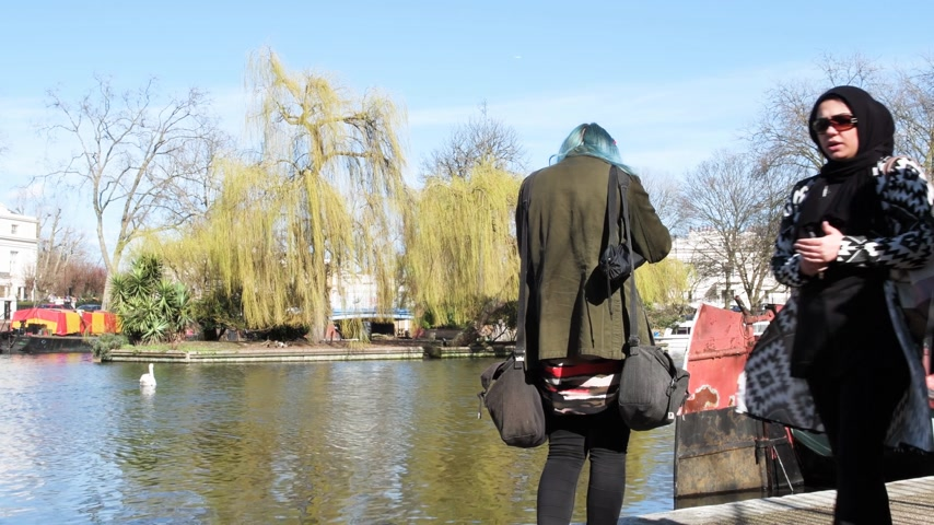 лодки : LONDON, UNITED KINGDOM - CIRCA 2018: Little Venice canal neighborhood - rear view of Caucasian woman taking photos of Robert Browning Island Muslim pedestrians nearby walking