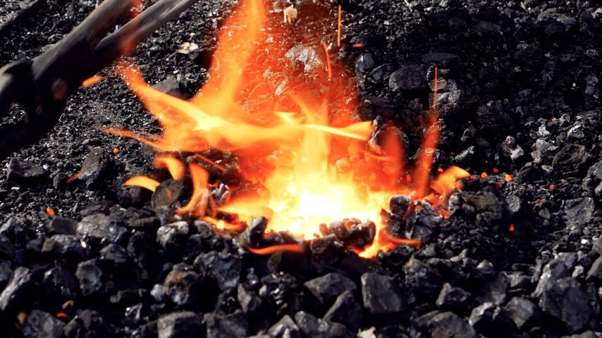 escovação : blacksmith forging fire with black coals and steel object in the burning fire - heating the object with the instruments and tools - steel manufacture