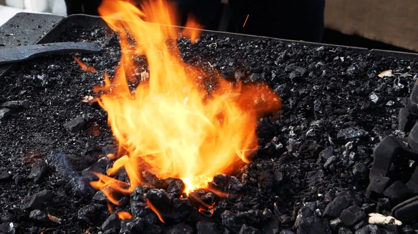 heating up metal : zoom out of slow motion - blacksmith forging fire with black coals and steel part in the burning fire instruments and tools