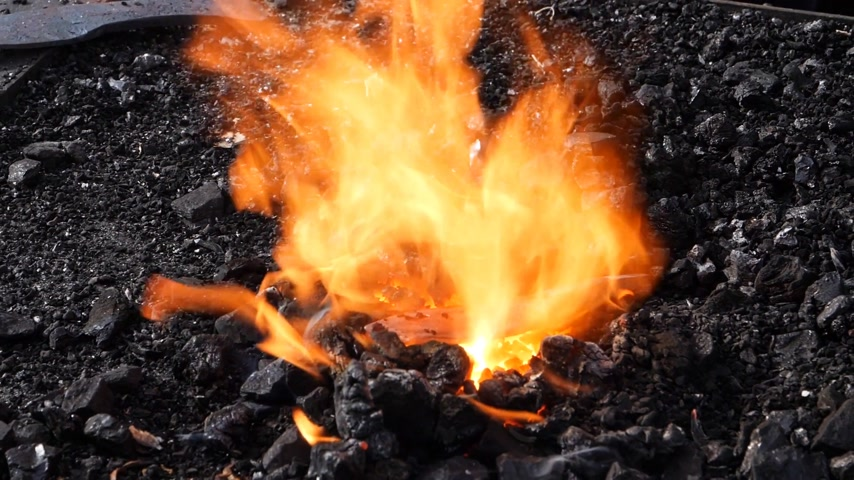heating up metal : Slow Motion of blacksmith forging fire with black coals and steel part in the burning fire Stock Footage