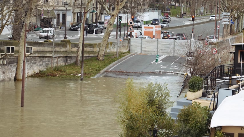 boathouse : PARIS, FRANCE - JAN 30, 2018: Houseboat barge peniche detail and flooded street covered with protection fence on the overflow flooding embankments on the Seine river in Paris