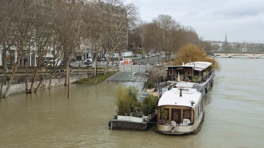 boathouse : PARIS, FRANCE - JAN 30, 2018: Houseboat barge peniche on the overflow flooding embankments on the Seine river news footage aerial of the Port Debilly