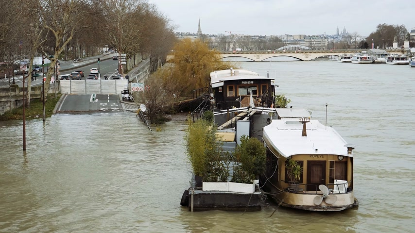 torrential rain : PARIS, FRANCE - JAN 30, 2018: Aerial view of houseboat barge peniche on the overflow flooding embankments on the Seine river in Paris after heavy rain