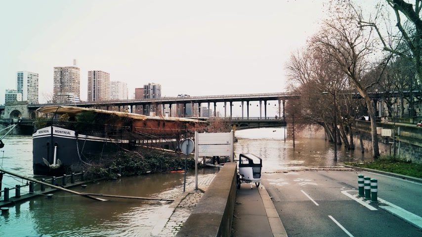 bir hakeim bridge : PARIS, FRANCE - JAN 30, 2018: Houseboat barge peniche on the overflow flooding embankments on the Seine river in Paris after heavy rains with Bir Hakeim Bridge in the background couple walking dog