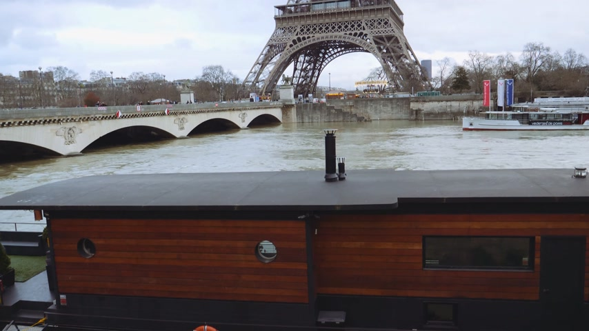 boathouse : PARIS, FRANCE - JAN 30, 2018: Houseboat barge peniche on bridge dIena with overflow flooding embankments on the Seine river in Paris after heavy rains with Eiffel Tower in the background Stock Footage