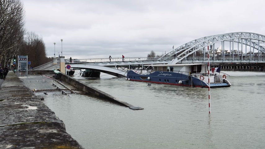 boathouse : PARIS, FRANCE - JAN 30, 2018: Closed street and promenade flooding embankments on the Seine river in Paris after heavy rains with with Passerelle Debilly bridge and people admiring the high waters