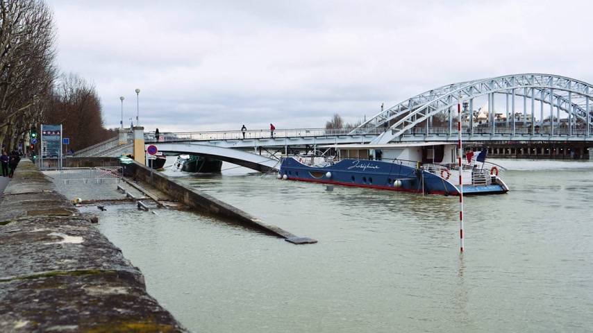 boathouse : PARIS, FRANCE - JAN 30, 2018: Closed street and promenade flooding embankments on the Seine river in Paris after heavy rains with with Passerelle Debilly bridge