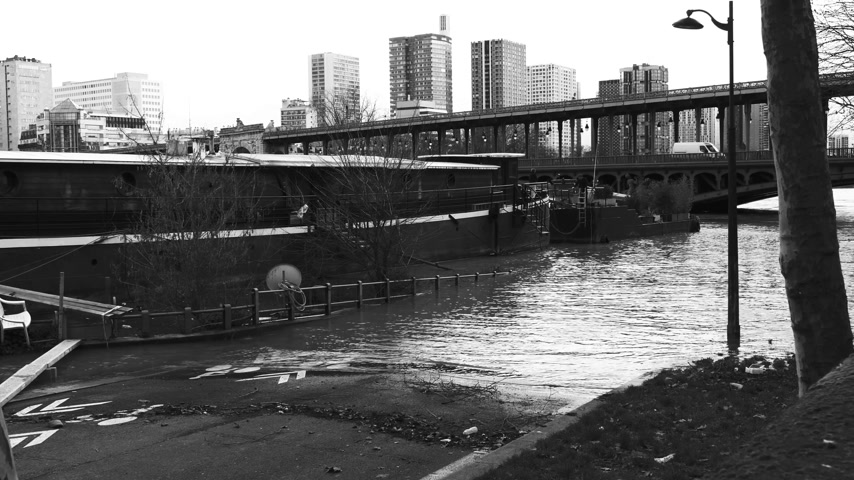 bir hakeim : Flooded Seine river with houseboat barge peniche on the overflow flooding embankments on the Seine river in Paris after heavy rains with Bir Hakeim bridge in the background - black and white Stock Footage