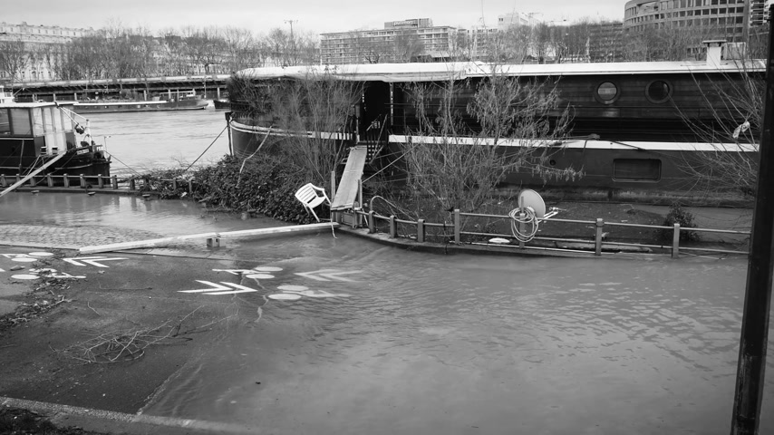 boathouse : View from above of flooded street and houseboat barge peniche on the overflow flooding embankments on the Seine river in Paris after heavy rain black and white