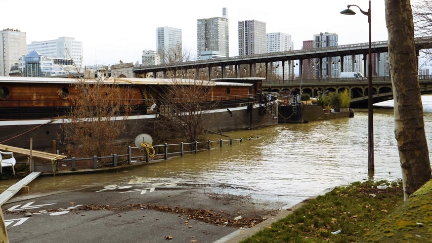 bir hakeim : Flooded Seine river with houseboat barge peniche on the overflow flooding embankments on the Seine river in Paris after heavy rains with Bir Hakeim bridge in the background